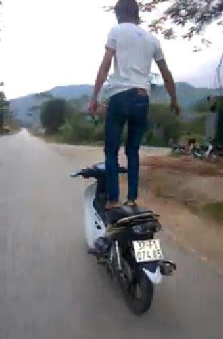 Thanh nien dung tren yen xe may dang chay - Anh 1
