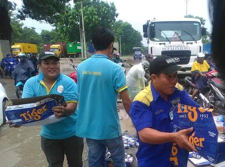 Binh Duong: Nguoi dan giup tai xe thu gom hang tram thung bia roi xuong duong - Anh 2