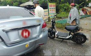 Vừa che ô vừa dùng điện thoại, cô gái đi xe đạp điện đâm thẳng đuôi ô tô