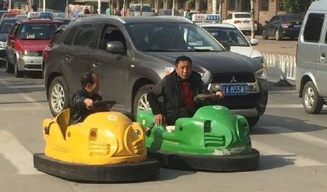 Hai nguoi dan ong Trung Quoc hon nhien lai xe dien ti hon tren pho - Anh 1