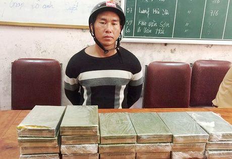 Giau 20 banh heroin trong ba lo roi chay xe may tu Lao ve Viet Nam tieu thu - Anh 1
