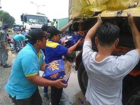Binh Duong: Nguoi dan giup tai xe thu gom hang tram thung bia roi xuong duong - Anh 1