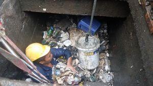 Công nhân ngâm mình dưới cống ở 'rốn ngập' Sài Gòn vớt rác