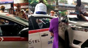 Bị CSGT Hà Nội thổi phạt, nữ tài xế taxi mặc váy lên nóc xe chửi bới