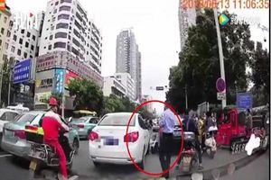Trung Quốc: CSGT gây sốc khi giả vờ bị ô tô tông, ngồi ăn vạ giữa đường