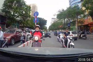 Người phụ nữ bị ô tô ép lùi vì chạy ngược chiều trên phố