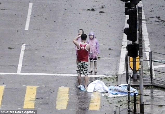 Bố bắt 2 con đứng co ro tạo dáng chụp ảnh trong siêu bão Mangkhut