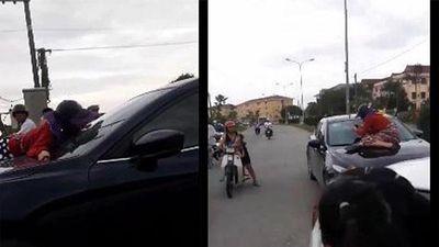 Vợ ngồi trên nắp capo đánh ghen, chồng vẫn lái xe chở tình nhân lao vun vút