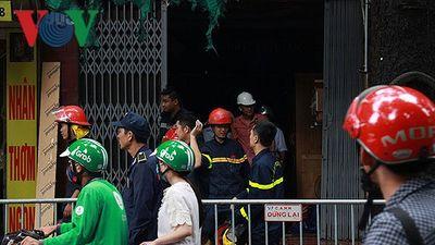 Lực lượng chức năng giúp dân gom đồ đạc sau vụ cháy ở Đê La Thành